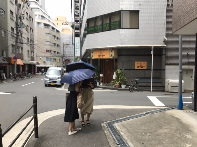 Women with umbrellas to protect from heat and sun are a common sight in the neighborhood. Shinmachi, Osaka, Japan