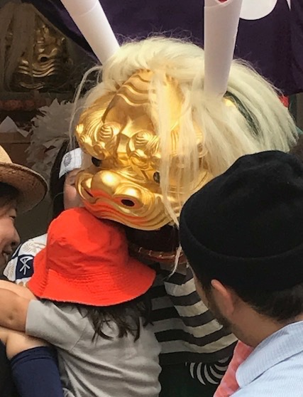 Child being blessed by Lion, Shishi, during Tenjin Matsuri Festival at Temmangu Shinto Shrine, Osaka, Japan. Photo by Sydney Solis.