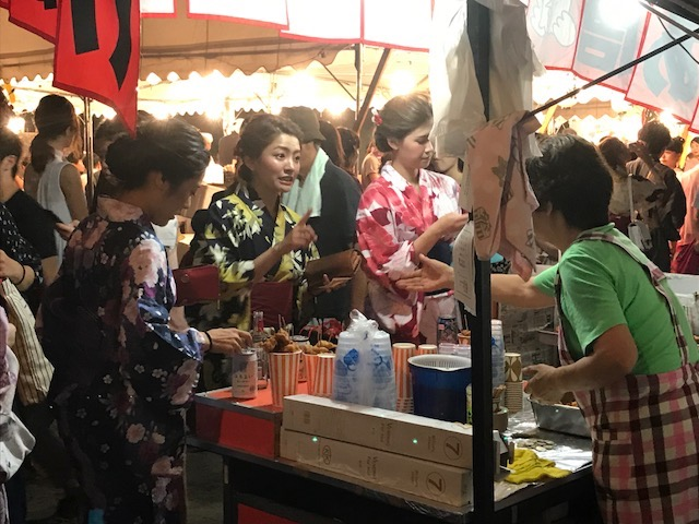 Women in kimonos out enjoying the evening during Tenjin Matsuri Festival, Osaka, Japan.