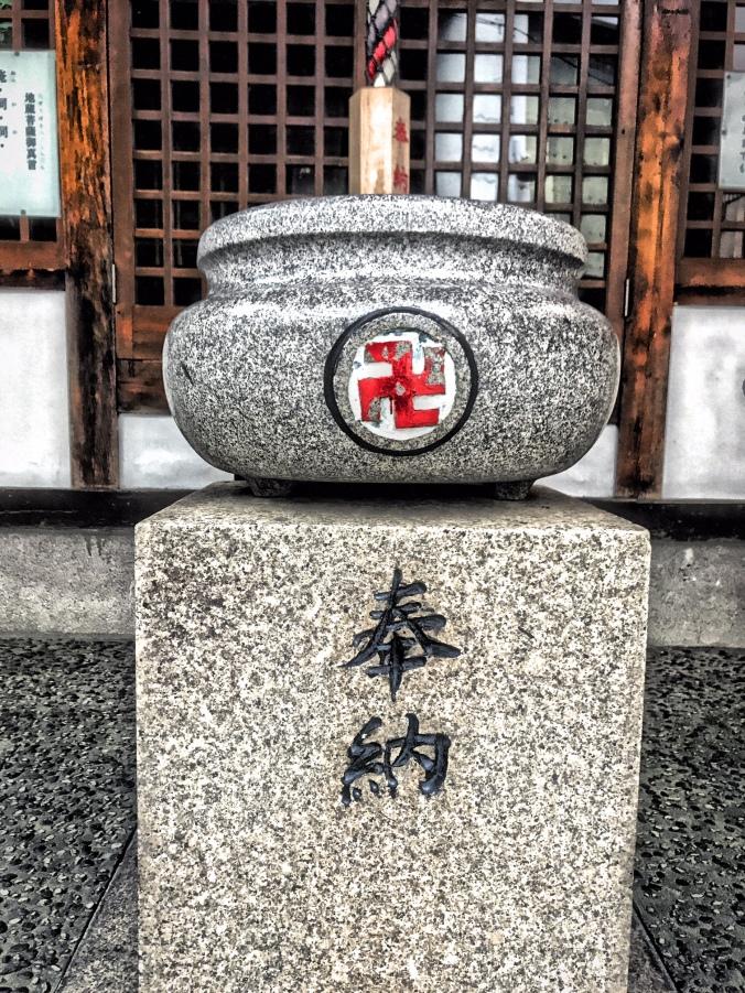 Shinto Shrine with swastika near Nishikujo Station in Osaka, Japan. Photo by Sydney Solis