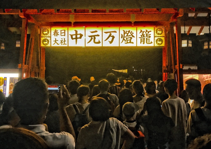Festival goers pass through a torii gate at Nara Park for Obon at the To-Kae festival, Nara, Japan. Photo by Sydney Solis