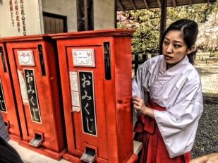 A Miko, shrine maiden, at Hirano Shrine fixes the fortune telling machine.