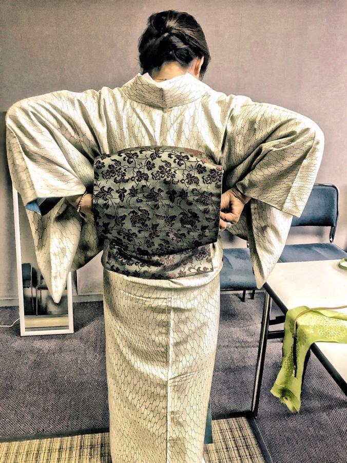 Yumi Ayama demonstrates putting on an antique obi with padding.