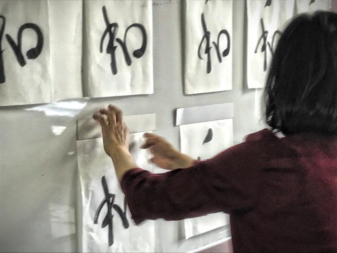 Noriko narrowing down my shodo work to the best ones.
