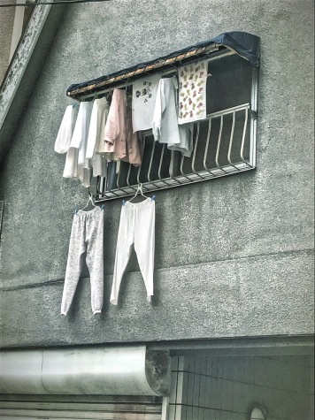 Clothes hanging on window, Osaka, Japan by Sydney Solis