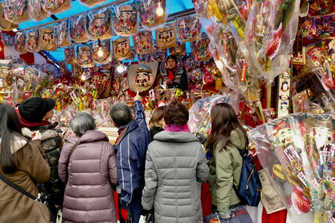Selecting lucky talismans of Ebisu in the merchant stalls outside of Imamiya Ebisu Shinto Shrine, Minami, Osaka, Japan
