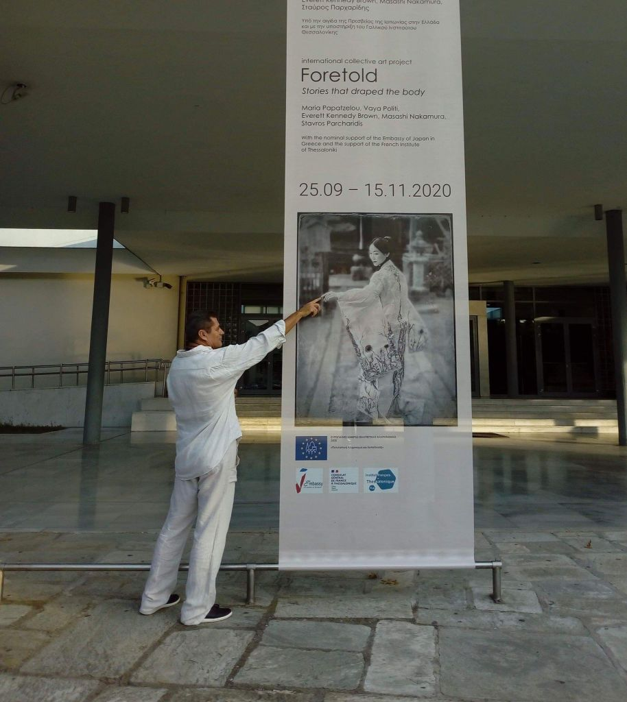 Exhibition Director, Videographer and Photographer Stavros Parcharidis in front of the Exhibition poster.